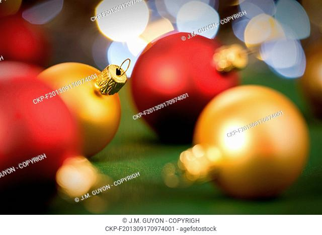 Gold and red christmas baubles on green lights background