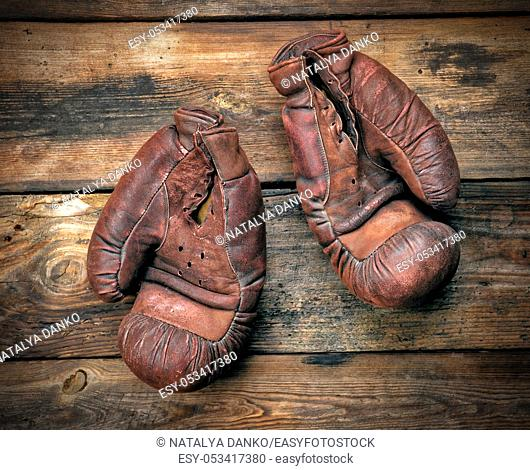 very old leather brown boxing gloves on a shabby wooden board