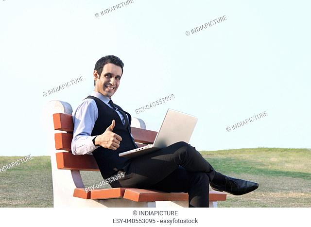 Portrait of businessman with laptop giving thumbs up , INDIA , DELHI