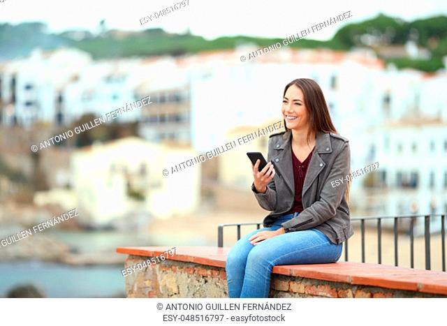 Happy woman holding smart phone contemplating views sitting on a ledge on vacation