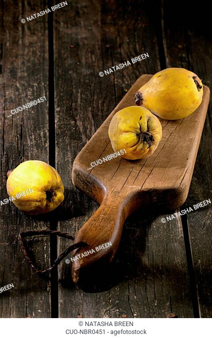 Three whole juicy quinces on old chopping board over wooden table in sunlight. Dark rustic style