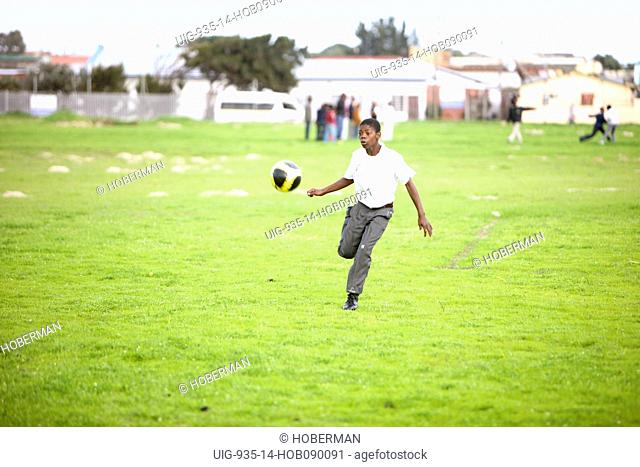School boy kicking Soccer Ball