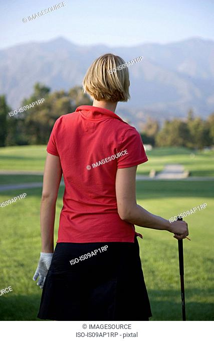 Young woman playing golf, rear view