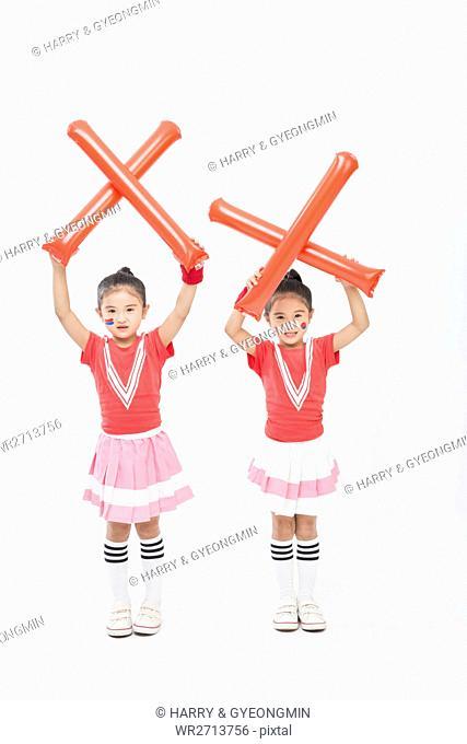 Smiling twin cheerleader girls