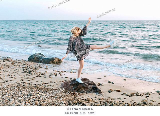 Young woman balancing on beach rock, Menemsha, Martha's Vineyard, Massachusetts, USA