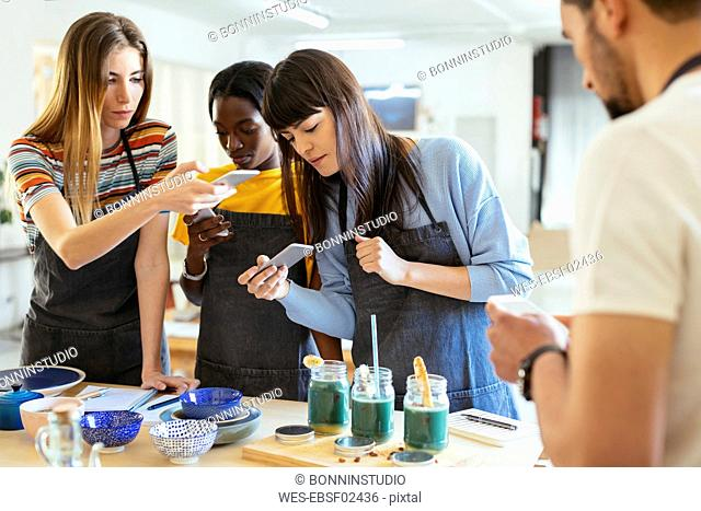 Friends taking smartphone pictures in a cooking workshop
