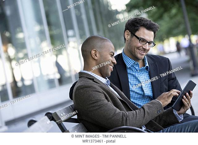Business people in the city. Keeping in touch on the move. Two men seated on a park bench outdoors, looking at a digital tablet