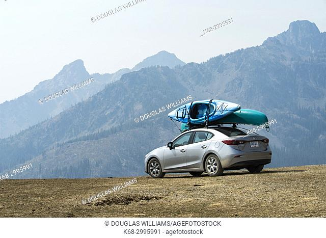 A car with canoe and kayak in the mountains of Idaho, near the Boise trail, with smoke from forest fires