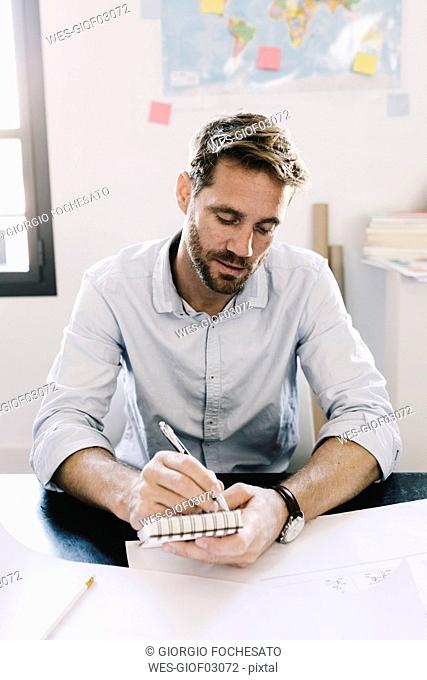 Portrait of architect sitting at desk taking notes