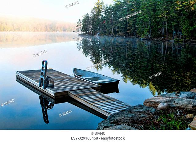 Dock with a fishing boat in the early morning mist in Haliburton County Ontario