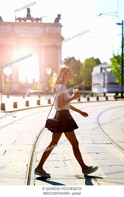 Italy, Milan, young woman walking in the city