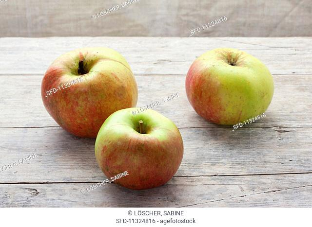 Three organic Ontario apples on a wooden surface