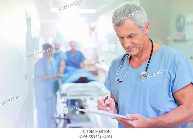 Mature male surgeon reviewing medical record clipboard in hospital corridor