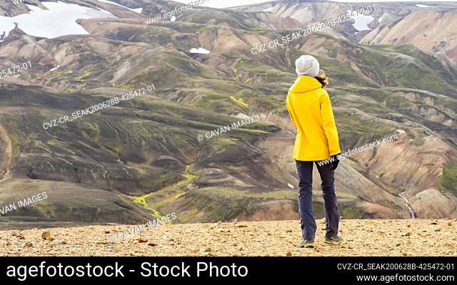 Bright woman hiker walking in Iceland's highlands mossy hills