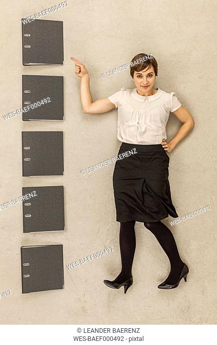 Businesswoman standing besides stack of files