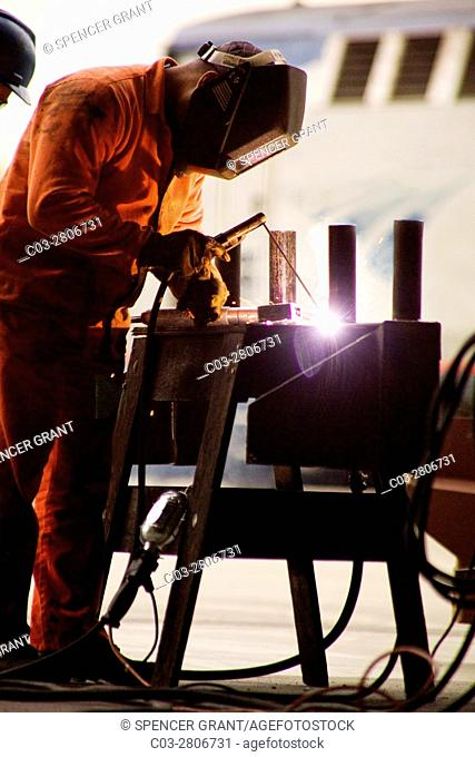 An arc welder makes a repair in a Los Angeles, CA, railroad yard. Note train in background