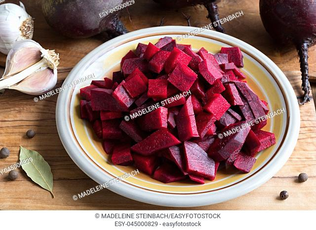Preparation of fermented beets - sliced red beets on a plate, with whole beets, onions, garlic and spices in the background