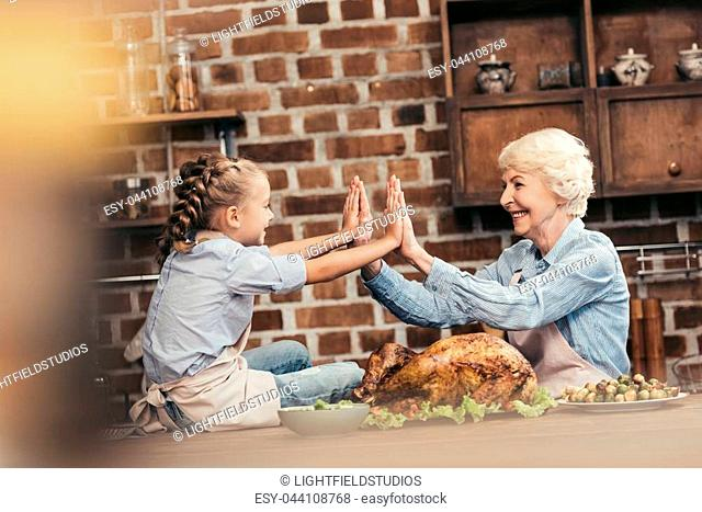 grandmother and granddaughter giving double high five on thanksgiving after successful turkey cooking