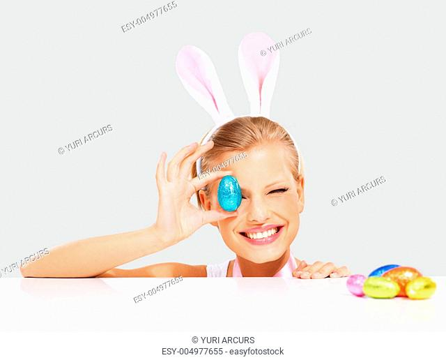Happy young woman wearing bunny ears and holding up a colorful Easter egg in front of her eye