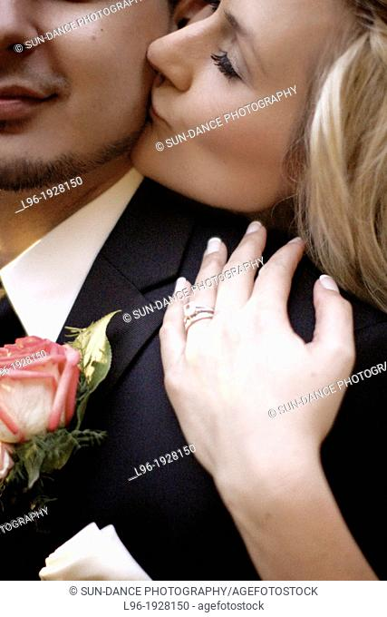 close-up photo of bride and groom stealing a moment alone on their wedding day kissing his cheek
