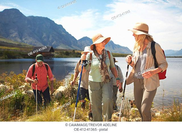 Active senior women friends hiking along sunny summer lake