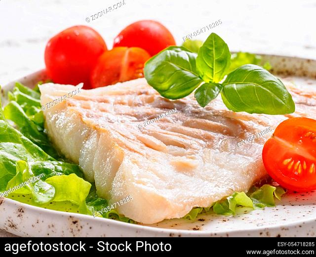 Close up view of grilled codfish with basil and cherry tomatoes in trendy white plate