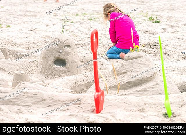 15 July 2020, Lower Saxony, Norddeich: A young girl is sitting behind a sand castle on the beach of Norddeich. Photo: Mohssen Assanimoghaddam/dpa
