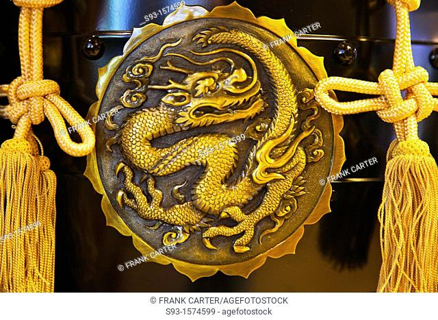 A close-up of a dragon design on a metal disk