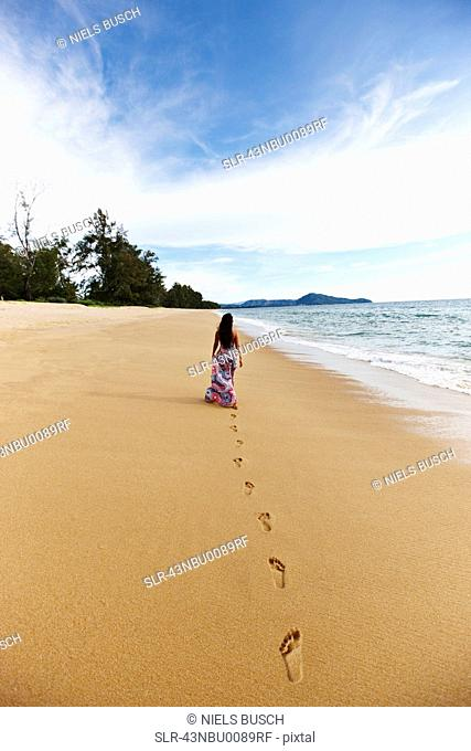 Woman making footprints on sandy beach