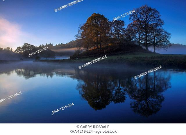 A calm clear autumn morning at Elterwater as the first light of a new day illuminates the trees and mist, Lake District National Park