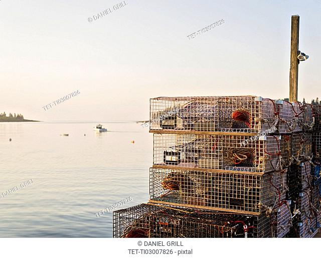 Stacks of lobster traps by sea at sunrise