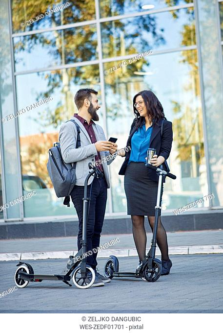 Happy businessman and businesswoman with scooters talking on pavement