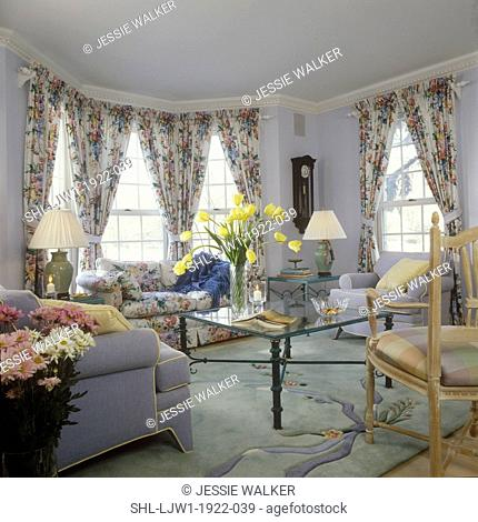 LIVING ROOM - Light blue living room, floral chintz drapes and sofa, rod pocket, bay window, glass and metal coffee table, yellow tulips, matching table lamps