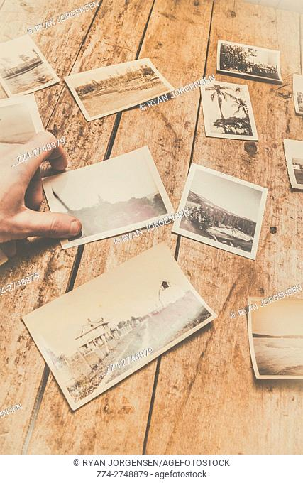 Close-up of unrecognizable male hand holding printed black and white photo on table with other polaroid shots. Vintage yellow color