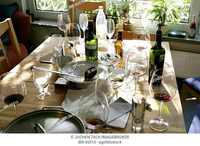DEU, Germany: Table with empty bottles, glasses after a party