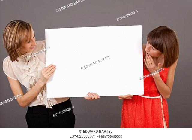 two surprised women with white banner