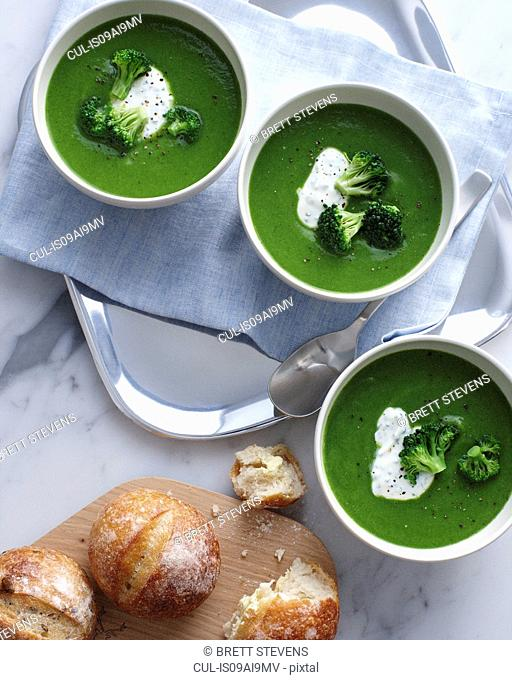 Still life of bowls of broccoli soup with sour cream