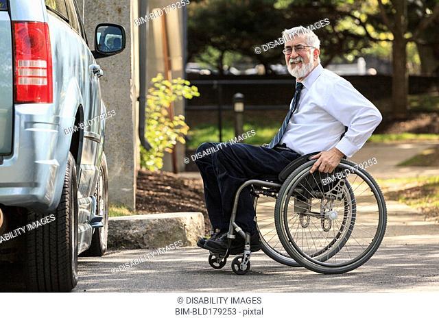 Caucasian businessman in wheelchair at van