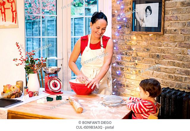 Mother making Christmas cookies, smiling at baby boy