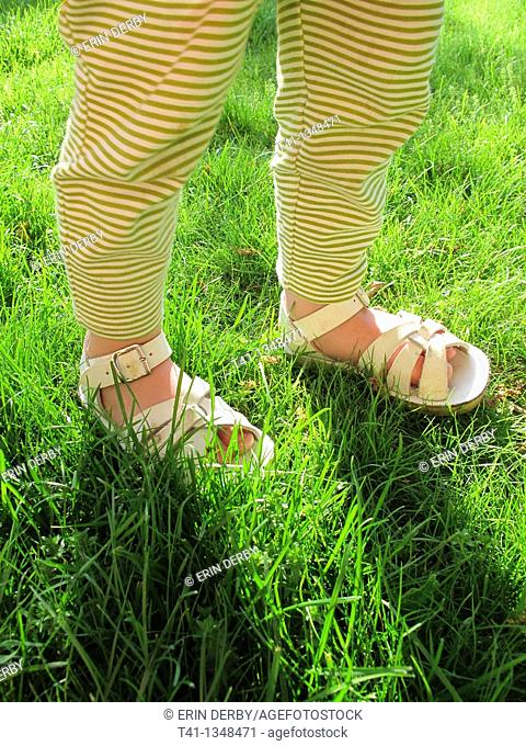 Baby feet in the long green grass