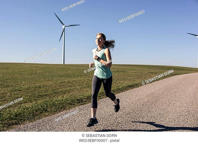Young woman jogging on field way, wind wheels in the background