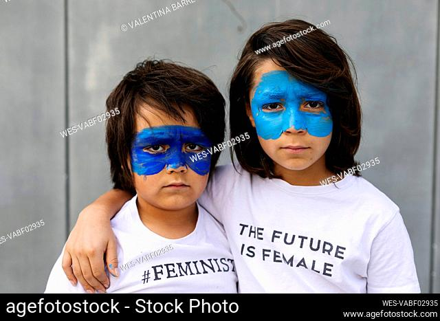Portrait of two brothers with painted blue masks on their faces wearing t-shirts with feministic imprints