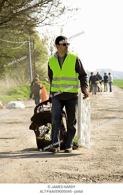 Volunteer cleaning up garbage dumped alongside road
