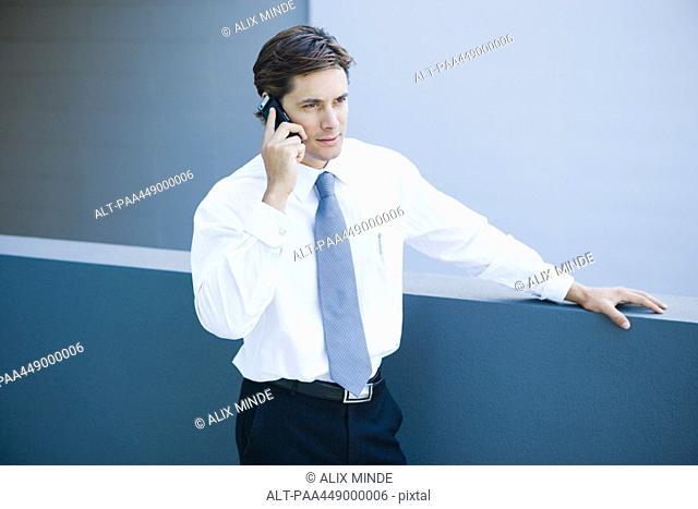 Businessman using cell phone, waist up