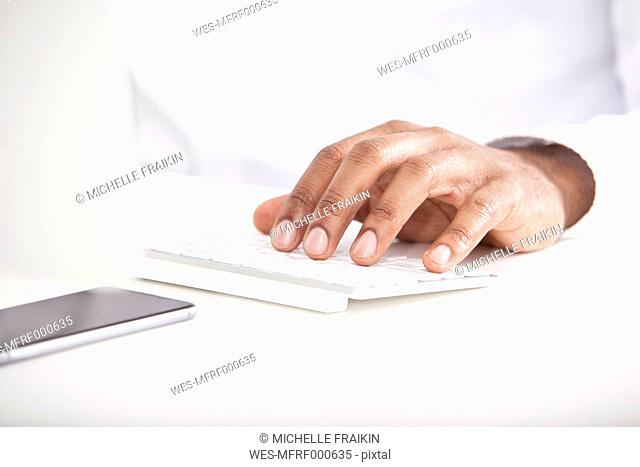 Man's hand typing on keyboard at white desk