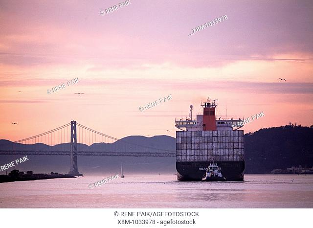A tug boat pushes a commercial container ship out toward the Oakland Bay Bridge and into the outer San Francisco Bay, California, USA