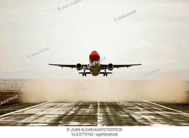 Plane with red cockpit is about to land. Horizontal outdoors shot