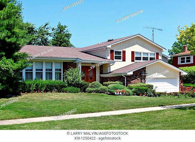 Brick home in suburbs with red shutters