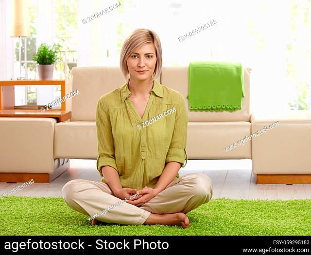 Smiling woman sitting with legs crossed on living room floor, looking at camera
