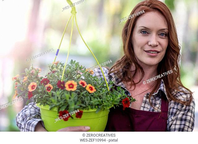 Woman in garden center with potted flowers